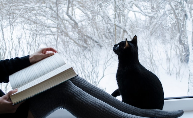 Reading woman with long socks sitting with black cat looking at the window with winter view