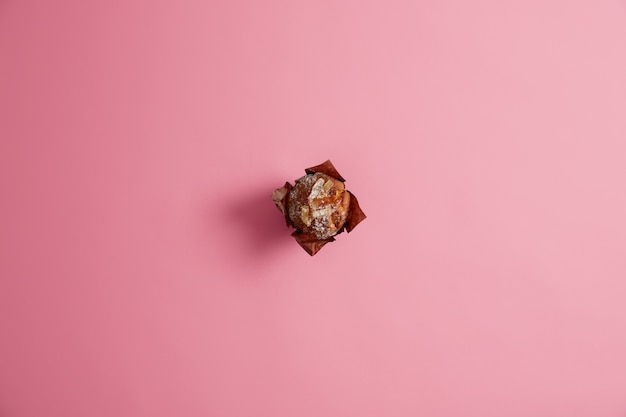 Ready baked muffin powdered with sugar in brown paper isolated on pink  background. fresh confectionery, sweet life, junk food concept. morning breakfast. dessert for gourmets. selective focus.