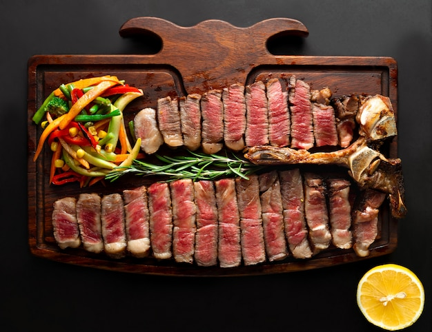 Ready to be served porterhouse steak with vegetables on wooden serving board