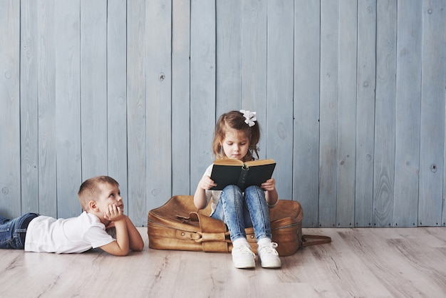 Ready to big travel. happy little girl and boy reading interesting book carrying a big briefcase and smiling. travel, freedom and imagination