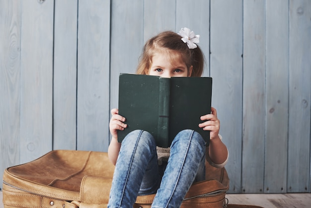 Ready to big travel. happy little girl reading interesting book carrying a big briefcase. freedom and imagination concept