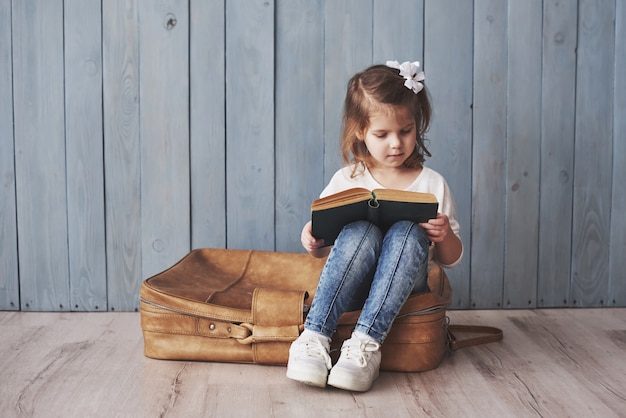 Ready to big travel. happy little girl reading interesting book carrying a big briefcase and smiling. travel, freedom and imagination