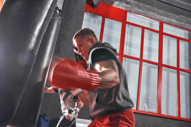 Ready to break his record young muscular athlete in sports clothing training hard on heavy