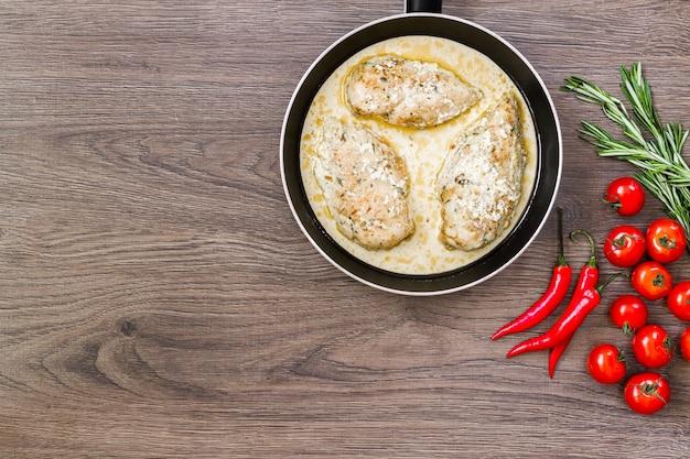 Готовая куриная грудка на сковороде со сливочным соусом.