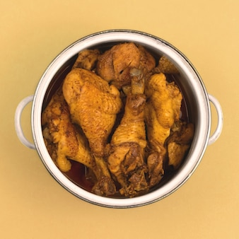 색상 배경의 냄비에 준비된 닭고기, 온 가족을 위한 식사 개념, 접시 위쪽 사진