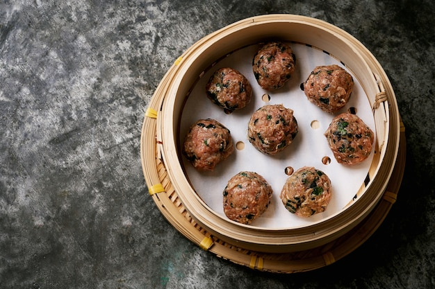 Ready to cook meatballs in asian bamboo steamer over a metal desk. top view. flat lay.