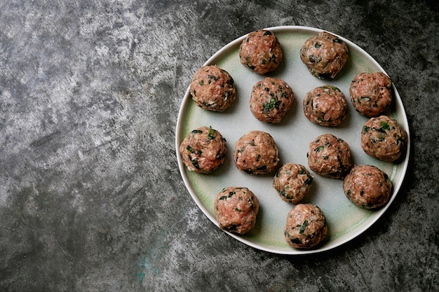Ready to cook meatballs in ceramic plate. flat lay. top view