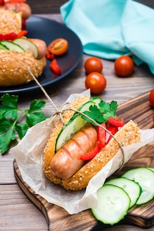 Ready-to-eat appetizing hot dog made from fried sausage, rolls and fresh vegetables, wrapped in parchment paper on a cutting board on a wooden table