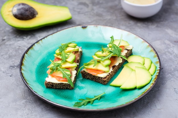 Ready-to-eat bruschettas with salmon, butter, avocado and arugula on a plate