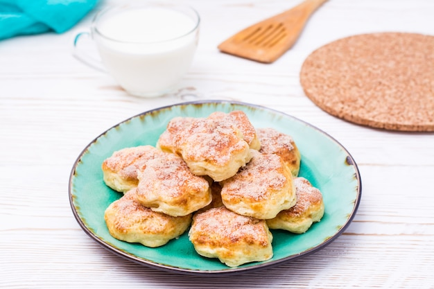 Ready-to-eat cottage cheese cookies on a plate on a wooden table.