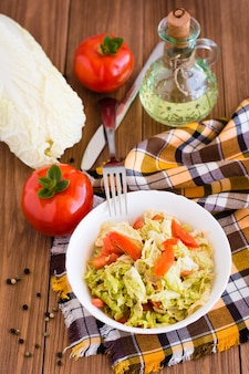 Ready-to-eat salad of tomatoes and peking cabbage in a plate, vegetables and a bottle of oil on a wooden table
