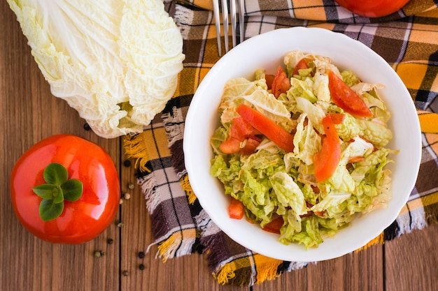 Ready-to-eat vegetable salad, tomatoes and chinese cabbage on a wooden table, top view