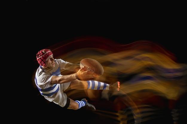 Pronto a volare per vincere. un uomo caucasico che gioca a rugby allo stadio in luce mista