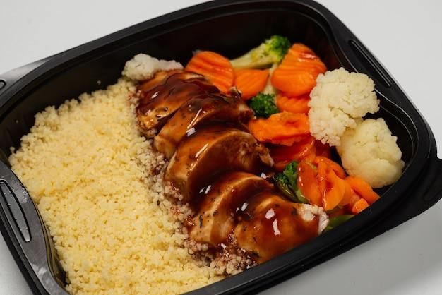 용기에 준비된 음식. 데리야끼 소스에 삶은 닭고기, 당근, 양배추, 죽. 흰색 배경에 고립.