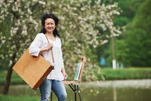 작업 준비. 악기 케이스를 든 성숙한 화가가 아름다운 봄 공원에서 산책