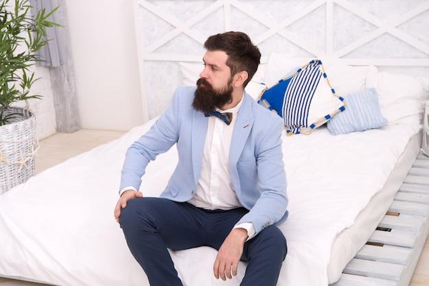 Готов к мальчишнику. холостяк с хипстерской бородой сидит на кровати. одинокий мужчина в строгой одежде. празднование дня холостяка. формальная мода. свадебный стиль. 11 ноября. день холостяка. завидный холостяк.