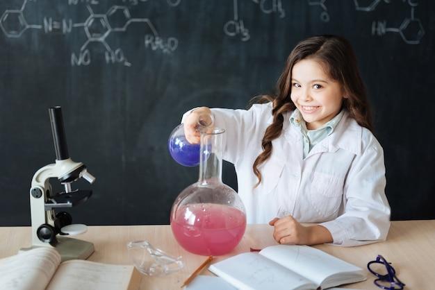 화학 발견을위한 준비. 실험실에 앉아 미생물 실험에 참여하고 전구를 사용하는 동안 화학 수업을 즐기는 즐거운 숙련 된 연구원 미소
