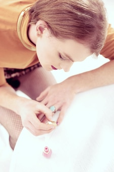 데이트 준비. 그의 짧은 남성 손톱을 칠하는 메이크업을 가진 즐거운 젠더 퀴어 남자
