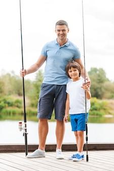 Готов к рыбалке. отец и сын в полный рост держат удочки и улыбаются, стоя на берегу реки вместе