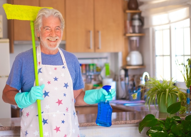 家事の準備ができました。魅力的な年配の男性が家の掃除用の物を持っています。