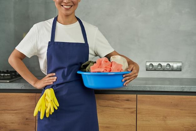 Готовы к работе по дому обрезанный снимок веселой молодой женщины, уборщицы, улыбающейся в камеру