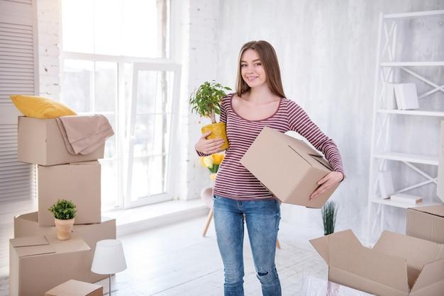 引っ越す準備ができました。アパートの真ん中に立って、植物と箱を持ってカメラに向かってポーズをとる美しい若い女性