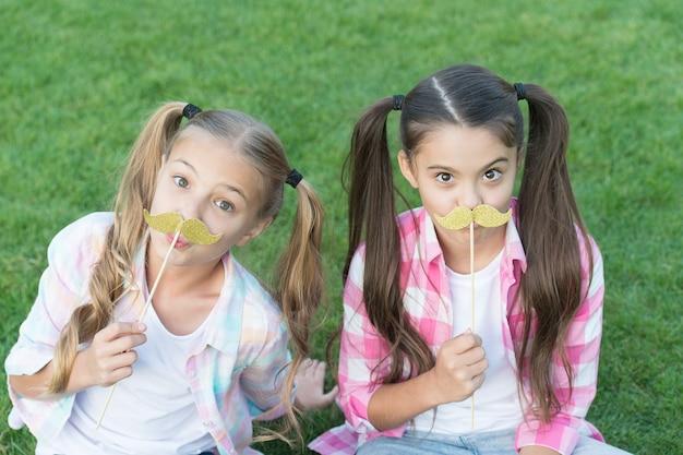 파티 준비. 어린 아이들은 콧수염 소품 푸른 잔디를 들고 있습니다. 막대기에 포토 부스 소품이 있는 작은 소녀. 파티 소품 및 액세서리. 축하를 위한 완벽한 소품. 여름 방학.