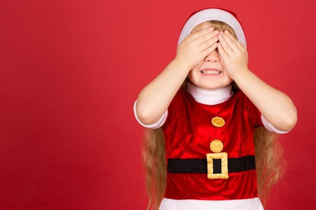 선물 준비. 넓게 웃고 그녀의 손으로 눈을 감고 산타 클로스 복장을 입은 작은 예쁜 소녀의 절반 길이 샷