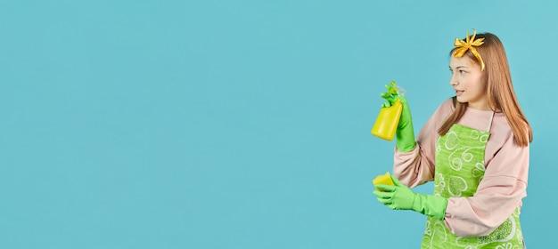 Готова к генеральной уборке. портрет радостной девушки с предметами домашнего обихода в руках над голубой стеной. молодая женщина держит бытовые чистящие средства и аэрозольные баллончики.
