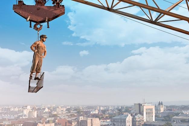 その日の準備ができました。超高層ビルのクレーンからぶら下がっているクロスバーでポーズをとる若い筋肉のレトロなビルダーのローアングルの肖像画