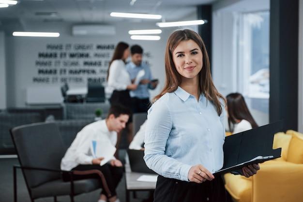 取引の準備ができています。バックグラウンドで従業員とオフィスに立っている若い女の子の肖像画