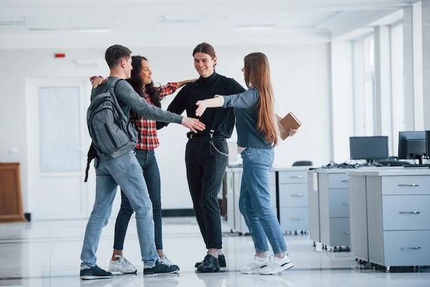 Готовы к хорошему рабочему дню. группа молодых людей, идущих в офисе во время перерыва