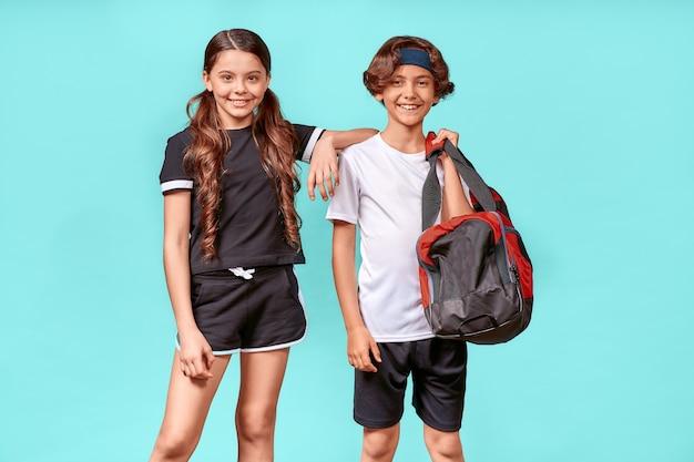 운동할 준비가 된 두 명의 행복한 십대 소년과 소녀는 운동복을 입고 카메라를 보고 웃고 있습니다.