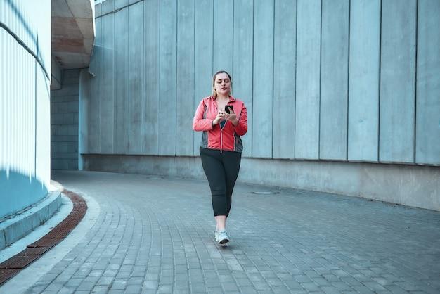 トレーニングの準備ができました。屋外に立っている間スマートフォンを保持しているスポーツ服の若いプラスサイズの女性。デジタルテクノロジー。スポーツコンセプト