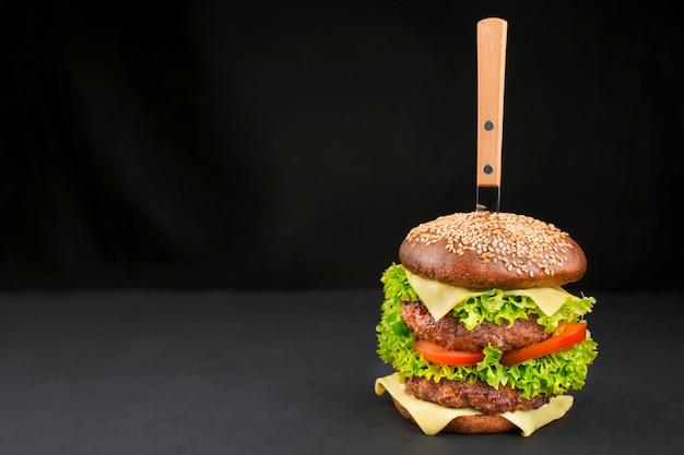 Готовый гамбургер с говяжьими котлетами, сыром, огурцом, свежими помидорами и салатом на темном фоне. продовольственный фон. быстрое питание. готовка. копировать пространство место для текста.