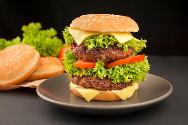 Готовый гамбургер с говяжьими котлетами, сыром, огурцом, свежими помидорами и салатом на тарелке. темный фон продовольственный фон. быстрое питание. готовка. крупный план.