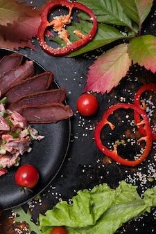 Готовый сытный мясной салат на темном фоне