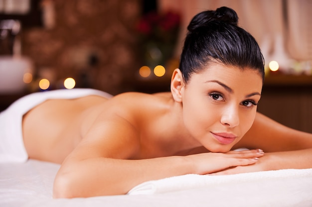 Ready for massage. beautiful young shirtless woman lying on massage table and looking at camera