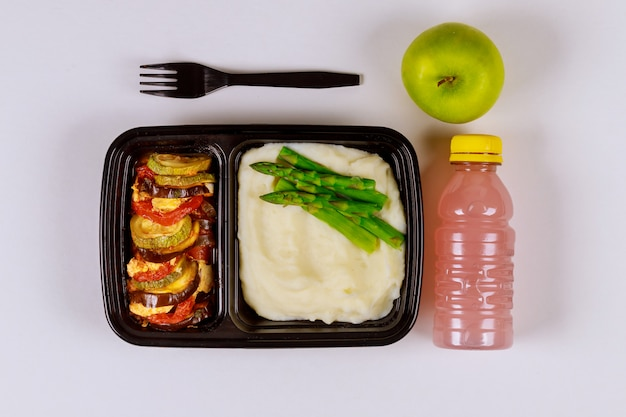 음료와 사과와 음식 용기에 먹을 준비가 된 식사.