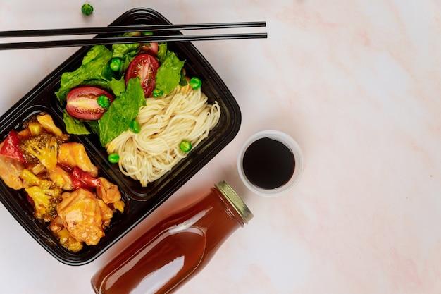 음료와 젓가락으로 음식 용기에 먹을 준비된 식사