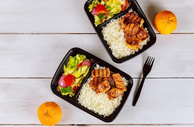 음료와 오렌지와 음식 용기에 먹을 준비가 된 식사.