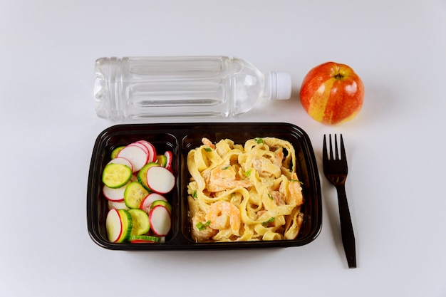 물과 사과와 음식 용기에 먹을 준비가 된 식사.