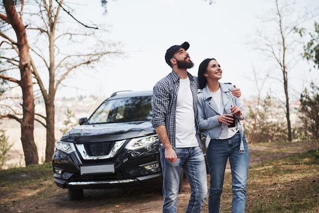 Ready for the new directions. embracing and enjoying the nature. couple have arrived to the forest on their brand new black car