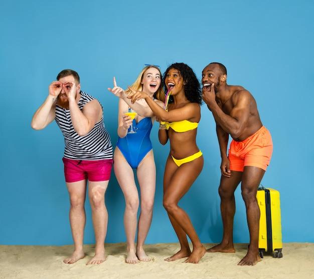 Pronto a far festa. giovani amici felici che riposano e che si divertono su sfondo blu studio. concetto di emozioni umane, espressione facciale, vacanze estive o fine settimana. freddo, estate, mare, oceano.