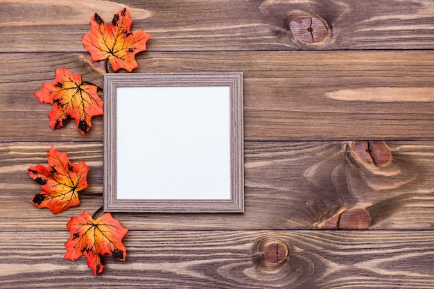 Ready photo frame on brown wooden background surrounded by orange maple leaves.