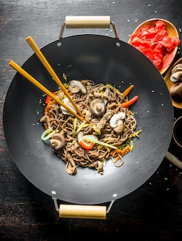 Ready soba noodles with ginger, mushrooms and soy sauce on dark rustic table