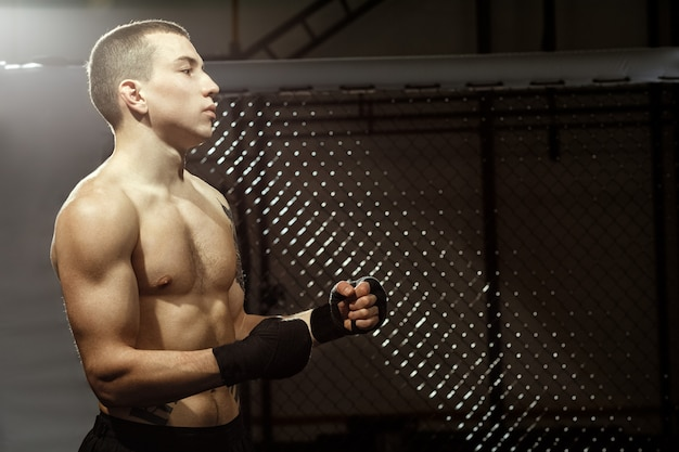 Ready for some pain? half length portrait of a young fit male fighter in a fighting cage