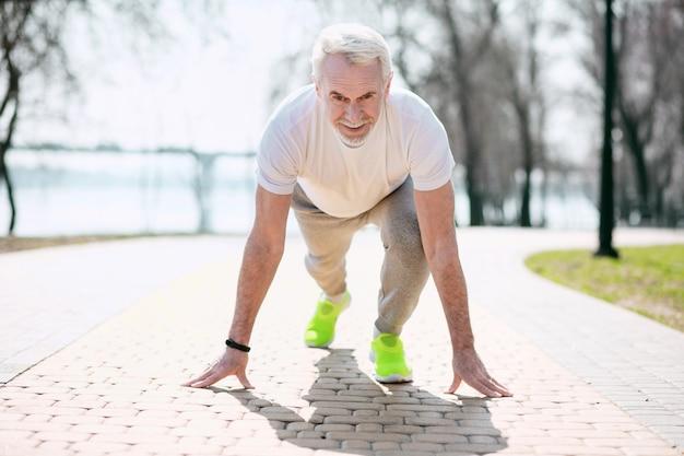 На старт, внимание, марш. восторженный зрелый мужчина готовится перед бегом в парке