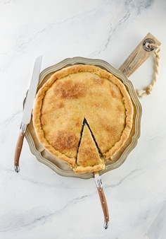 Ready swiss pie with chard, rice, onions and pine nuts on a wooden stand on white marble. flat lay