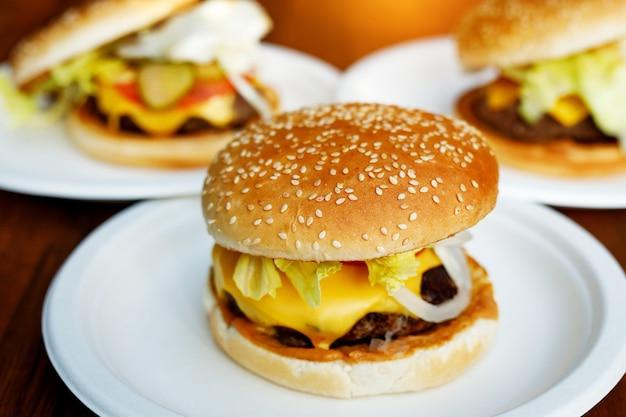 Готовые вкусные бургеры на круглых белых тарелках